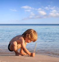 Picture of Little Boy at the Beach Writing in the Sand